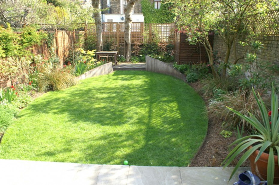 North London garden with oval lawn and raised timber beds